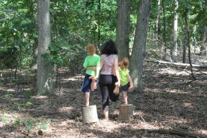 mom and two kids yoga in the woods