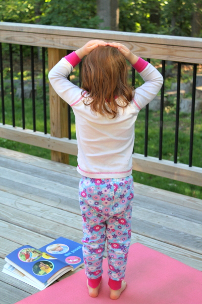 preschooler doing yoga on a deck with Yoga Kids book