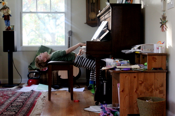 child playing piano in messy home